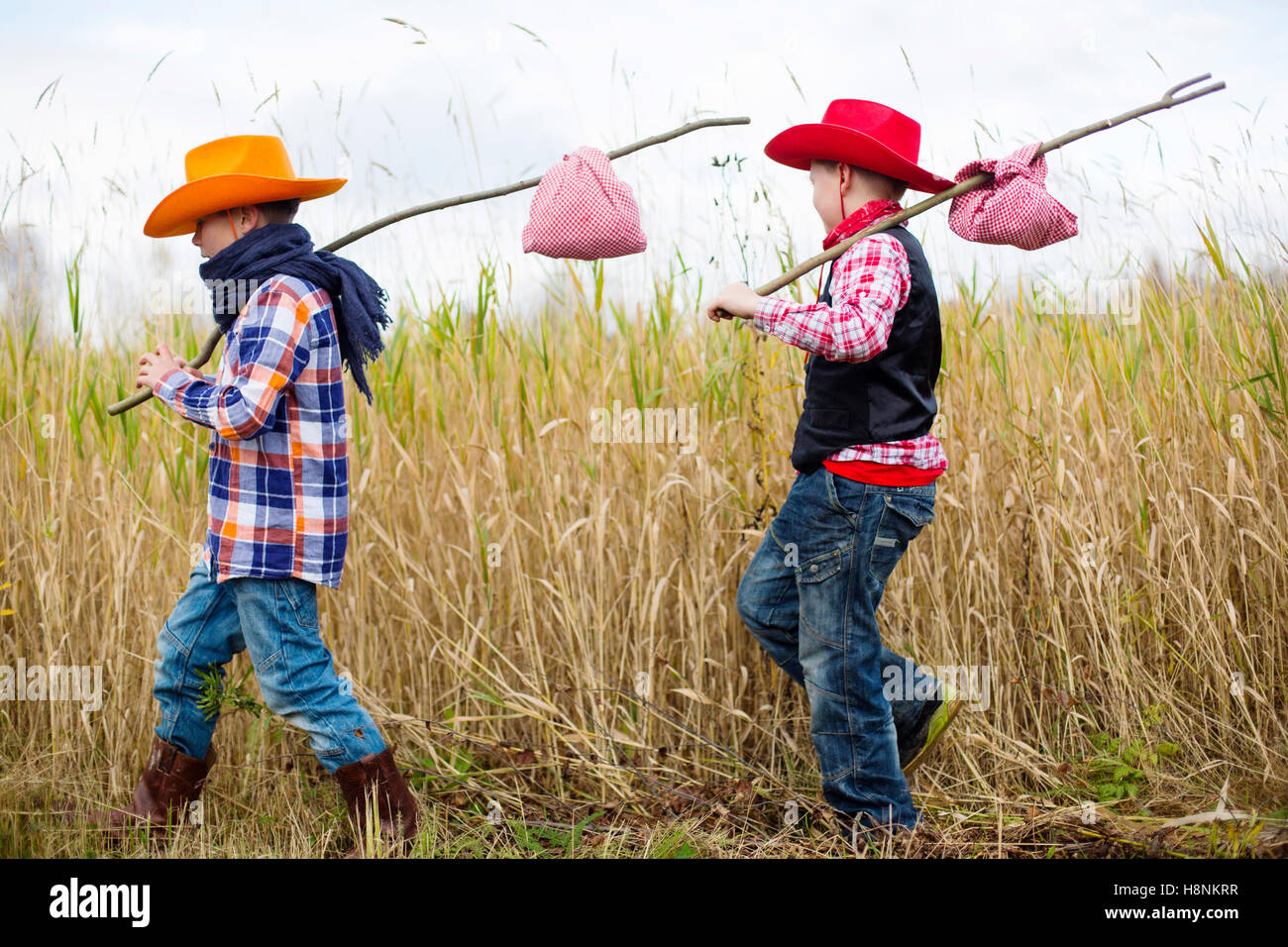 Boys (8-9) dressed up as cowboys walking in field - Stock Image