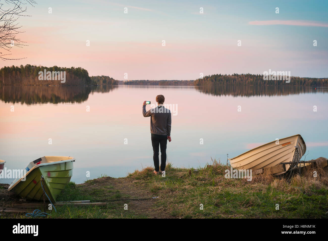 Mid adult man taking pictures on lake shore - Stock Image