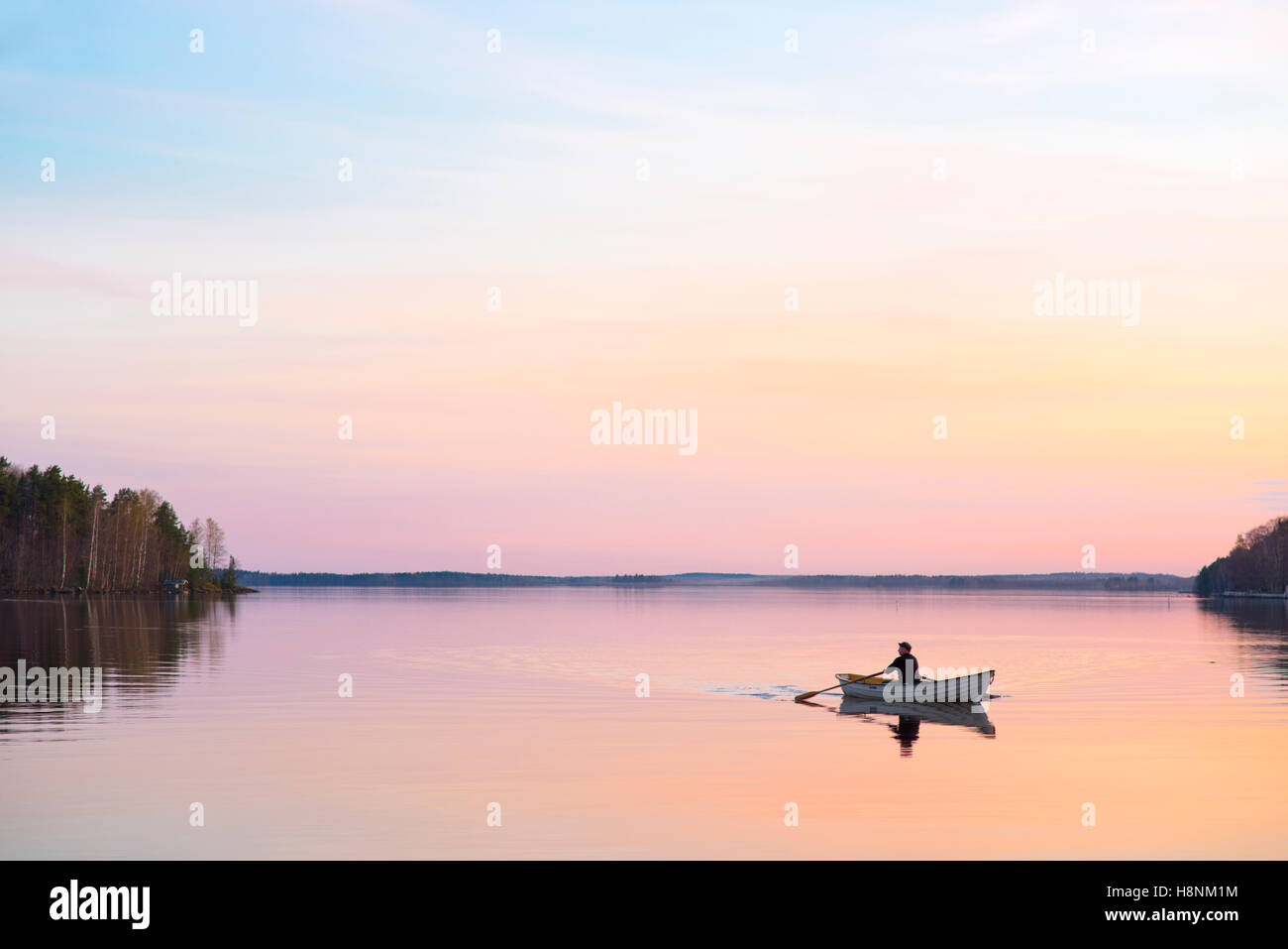 Man in boat on lake - Stock Image