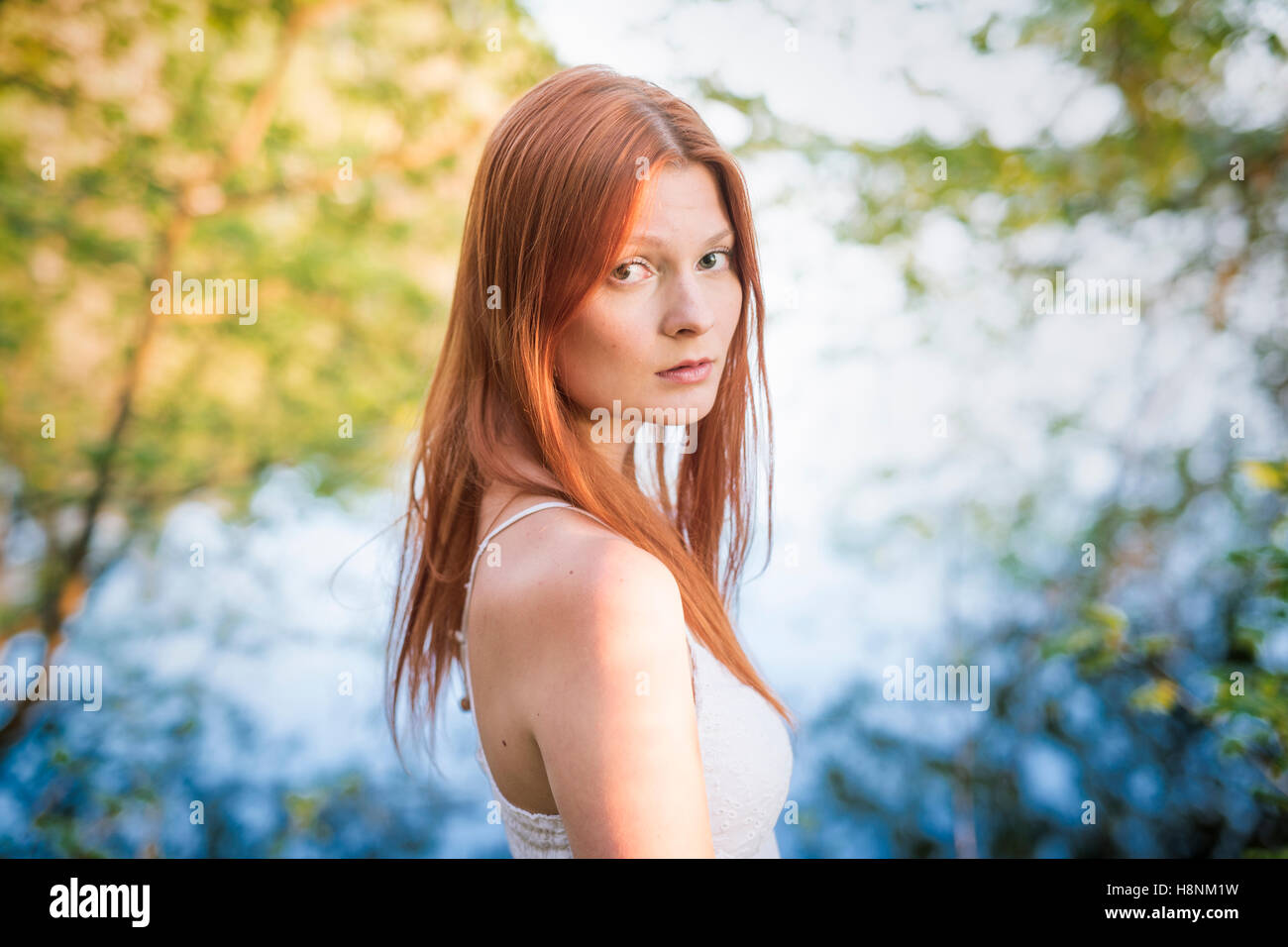 Portrait of young woman in forest - Stock Image