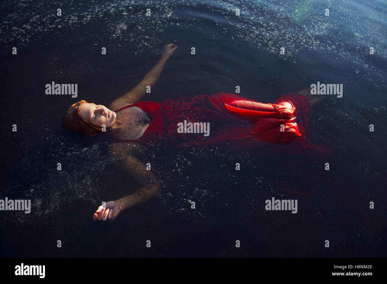 Woman in red dress floating on water - Stock Image