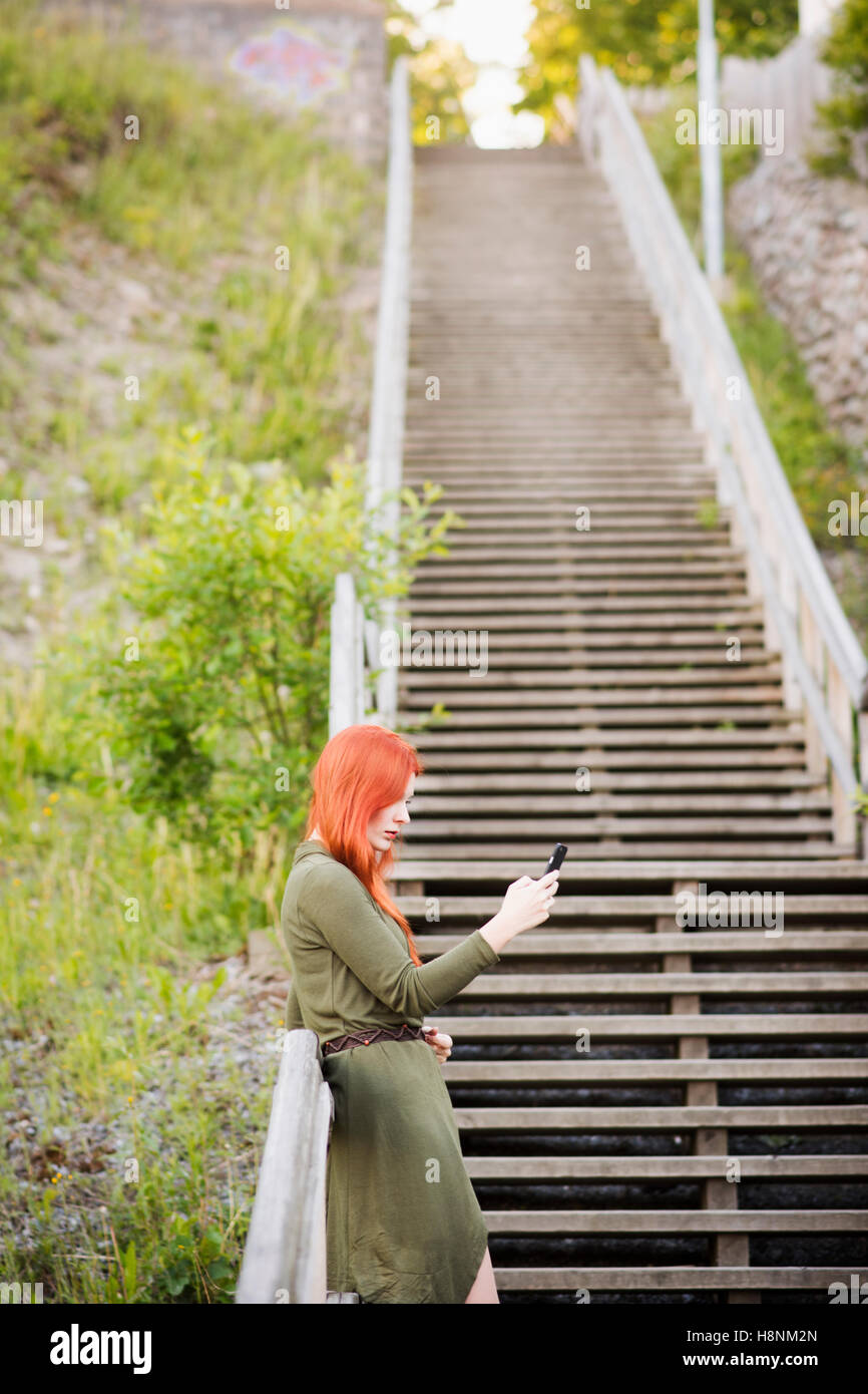 Redhaired woman standing on staircase and using phone - Stock Image