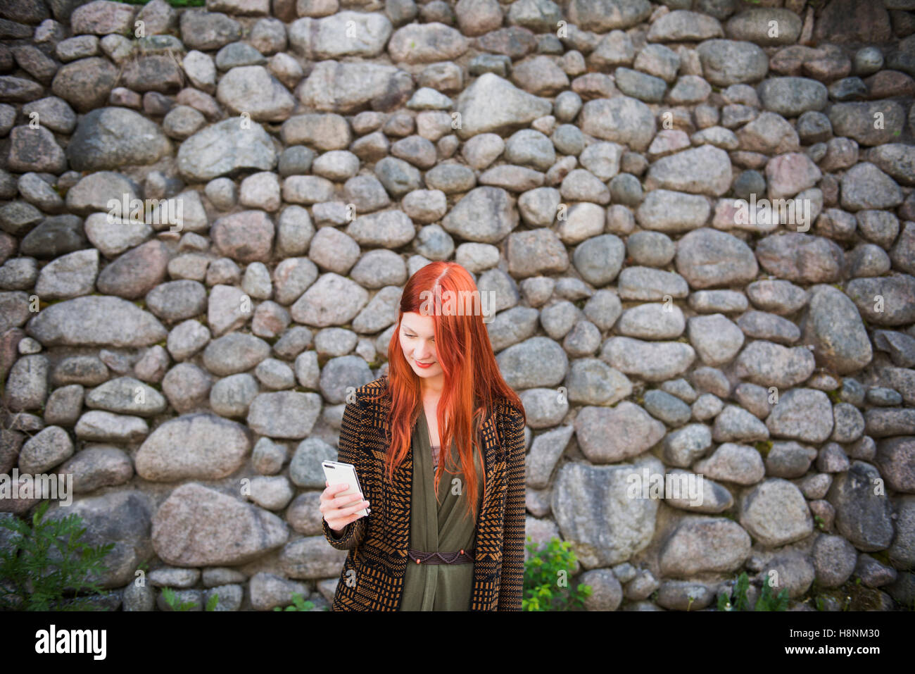 Redhaired woman standing against stone wall and using phone - Stock Image