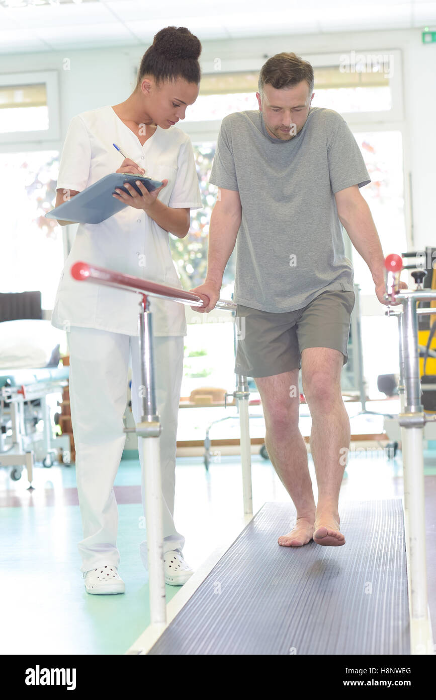 male patient standing with a physiotherapist - Stock Image