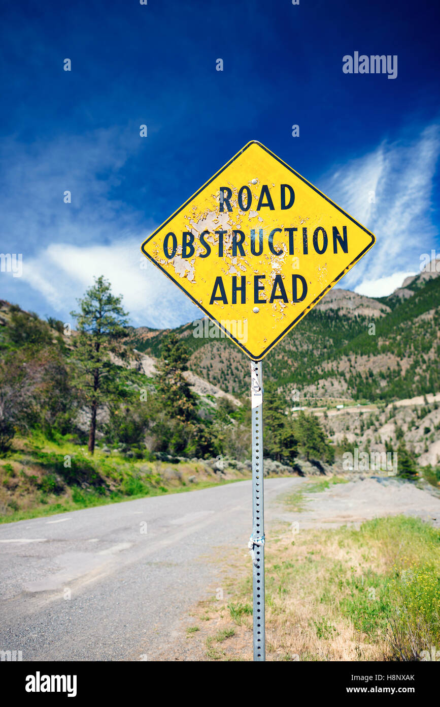 A sign warns of a road obstruction ahead. - Stock Image
