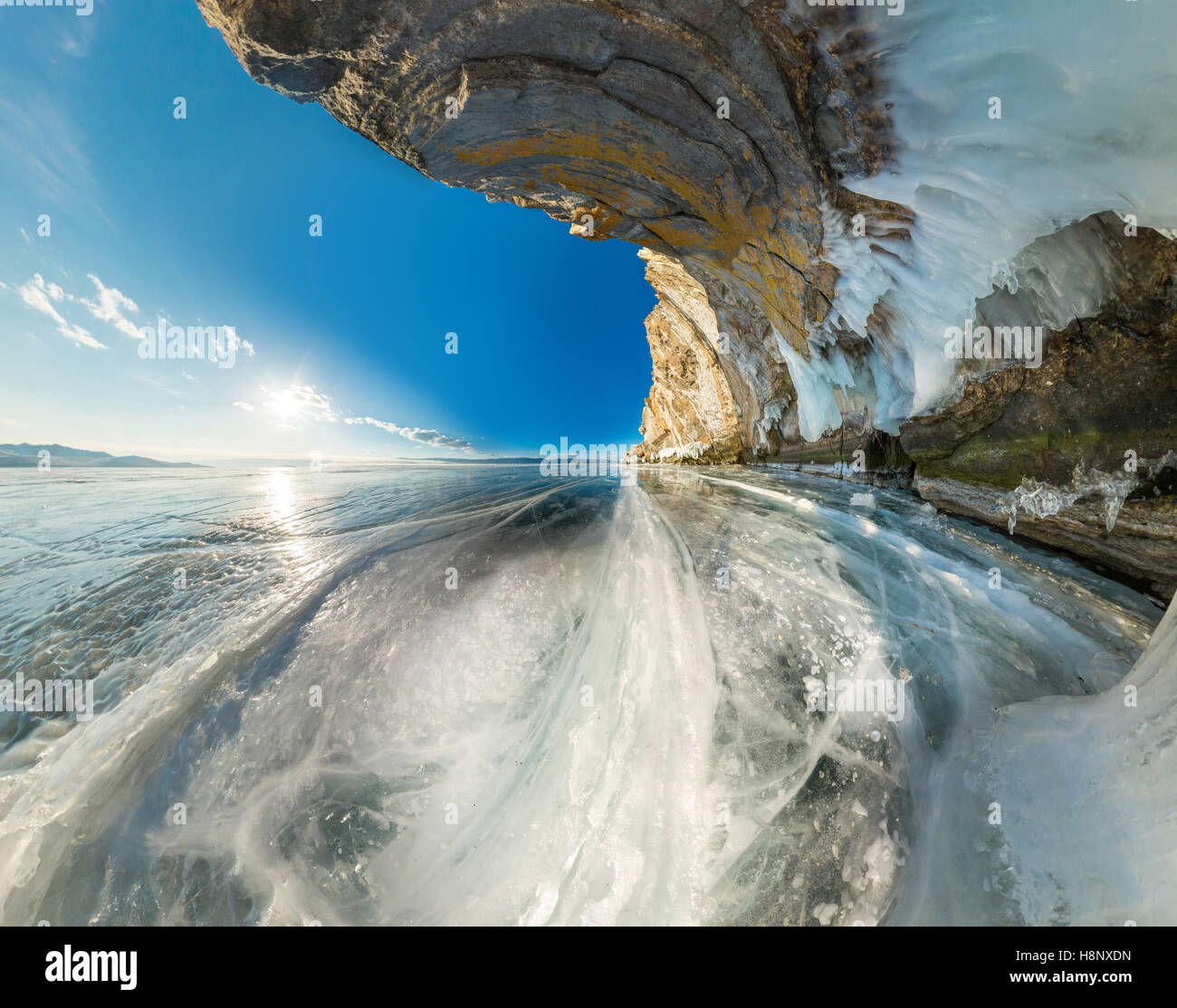 Ice grotto in rock on Olkhon Island on Lake Baikal ice covered wide-angle panorama. - Stock Image