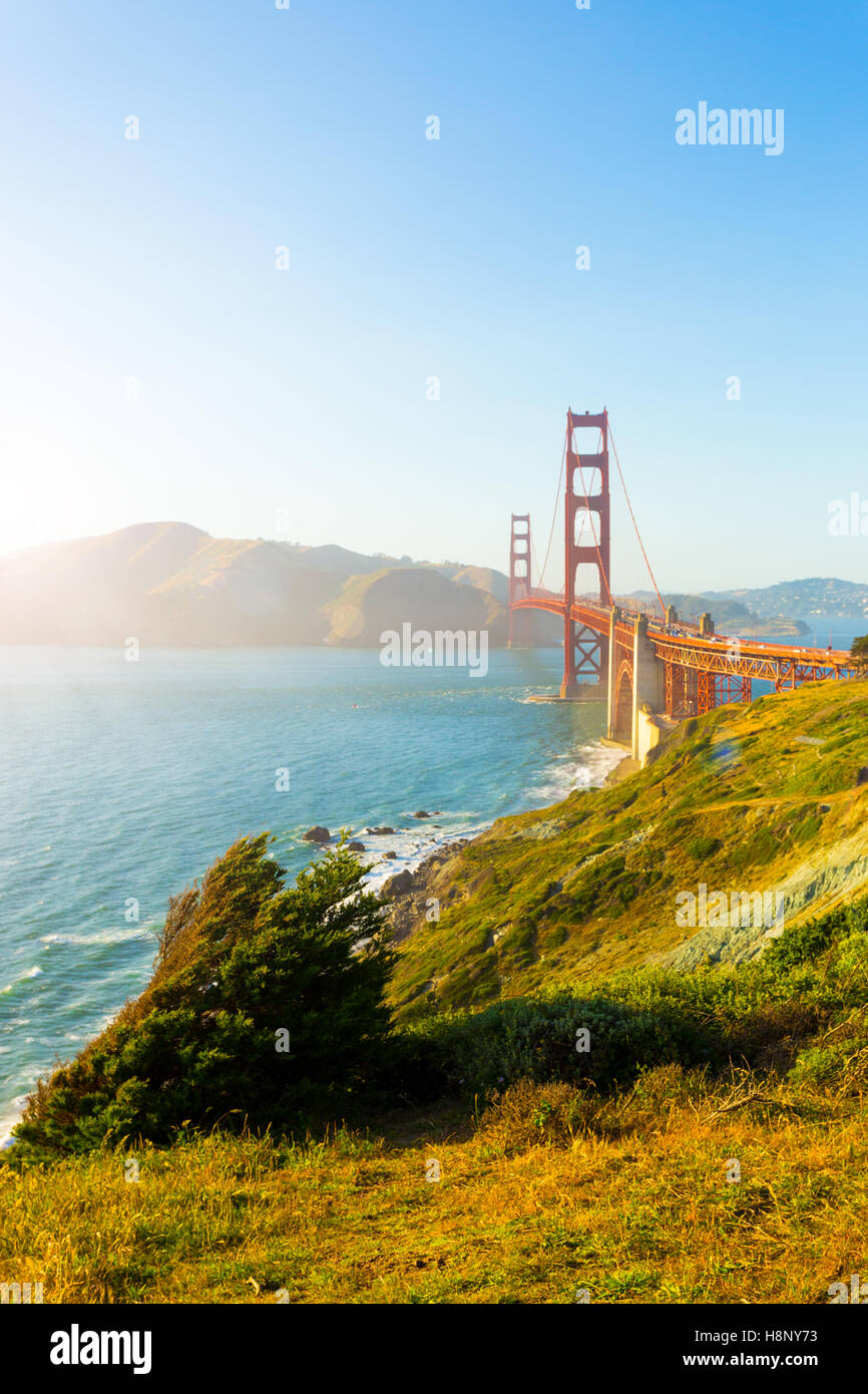 Sunlight provides high key highlights over Marin Headlands with Golden Gate Bridge seen over rocky coastline at - Stock Image