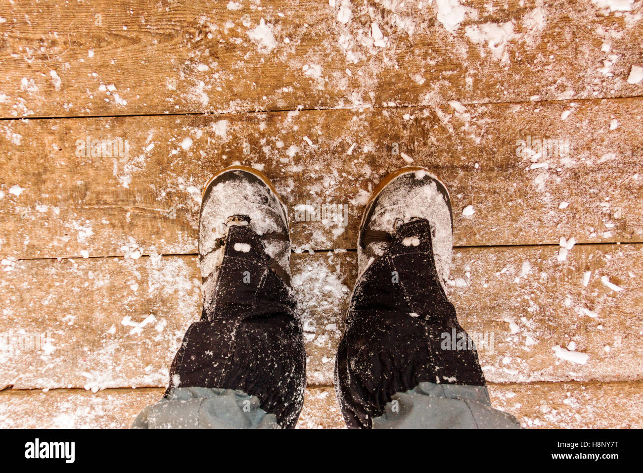 Top view of feet in boots and gaiters snow protection in the snow on the wooden floor. - Stock Image