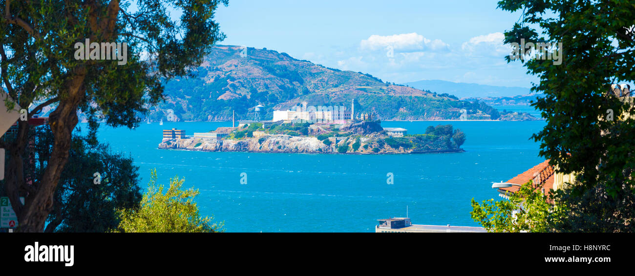 Wide panoramic telephoto view of Alcatraz Federal Penitentiary and island in middle of San Francisco bay framed - Stock Image