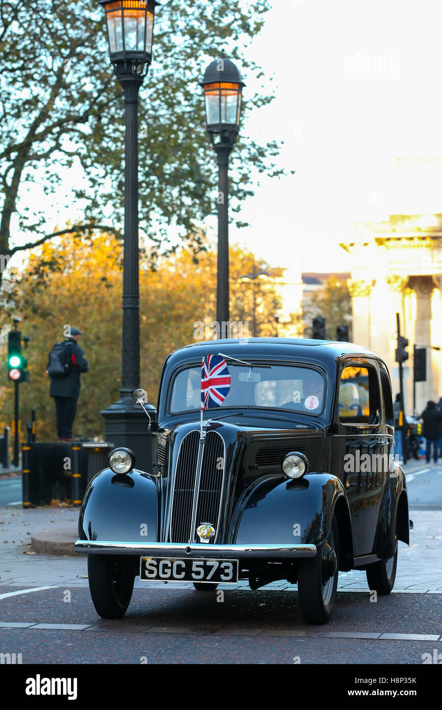 A portrait colour image of a black 1955 Ford Popular drives through a london street with union jack flag on the - Stock Image