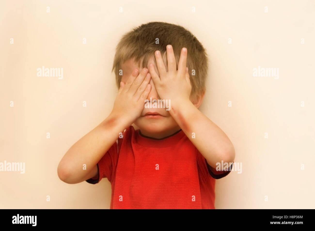 A conceptual image  of an abused child hiding his face.  Digitally enhanced. - Stock Image