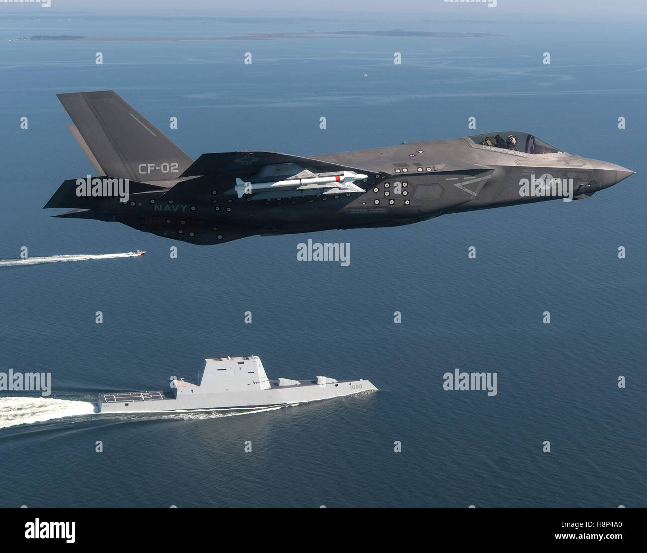 A F-35 Lightning II stealth multirole fighter aircraft flies over the USN Zumwalt-class guided-missile destroyer - Stock Image