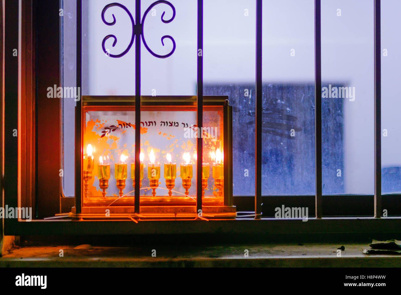 Traditional Menorah (Hanukkah Lamp) with olive oil candles. Text is: Candle of Mitzvah (commandment), Torah (Pentateuch) - Stock Image