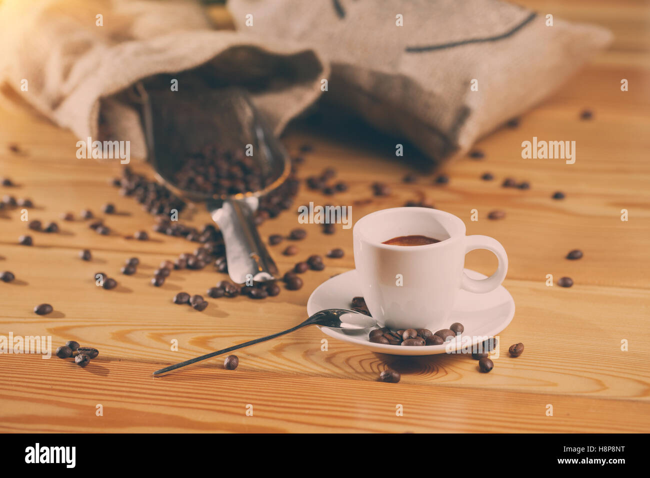 Cup of coffee, bag and scoop on old wooden background - Stock Image