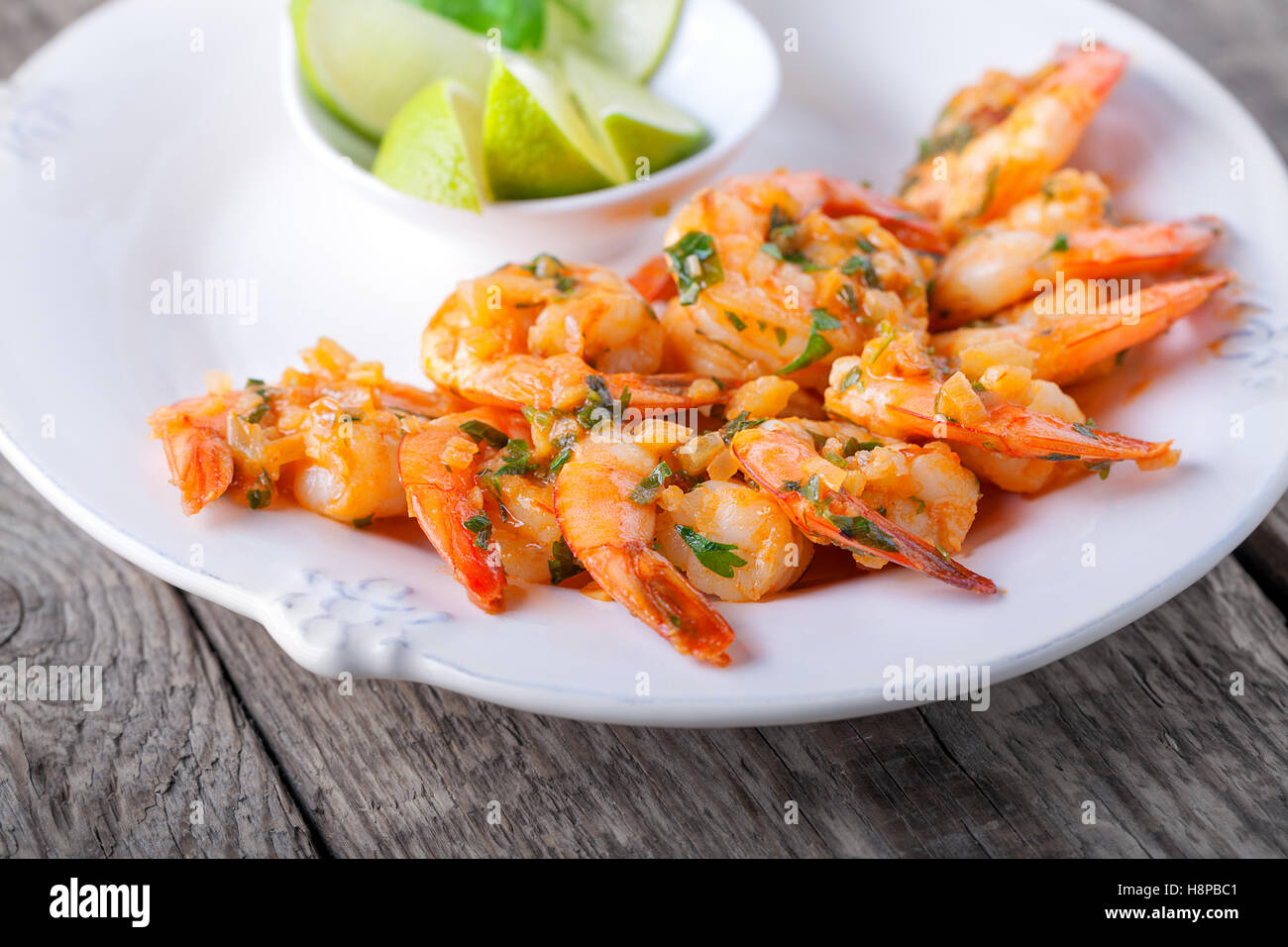 Fried Prawns served on the plate with lime - Stock Image