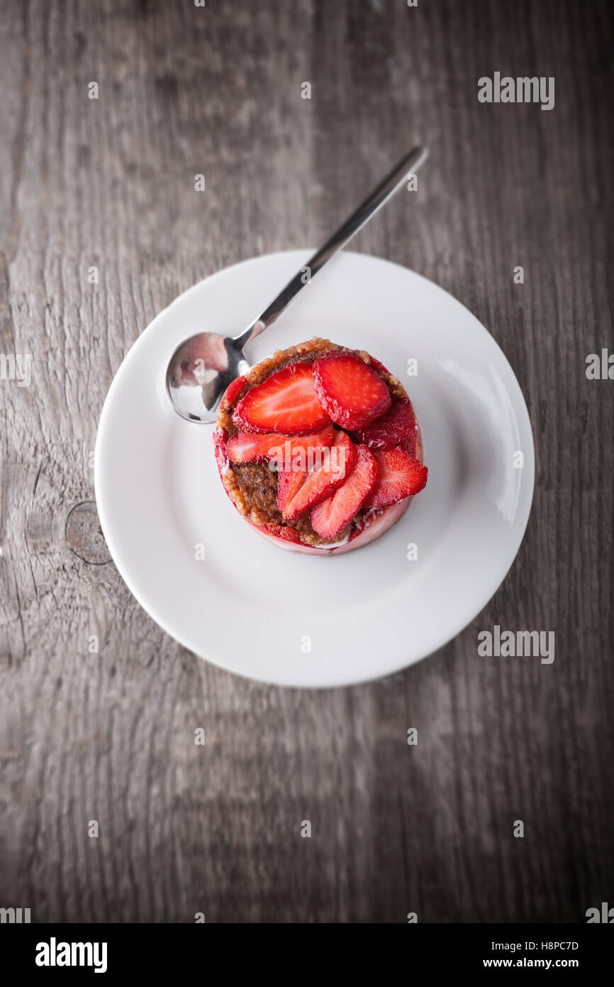 Strawberry and custard tart on a white plate. - Stock Image