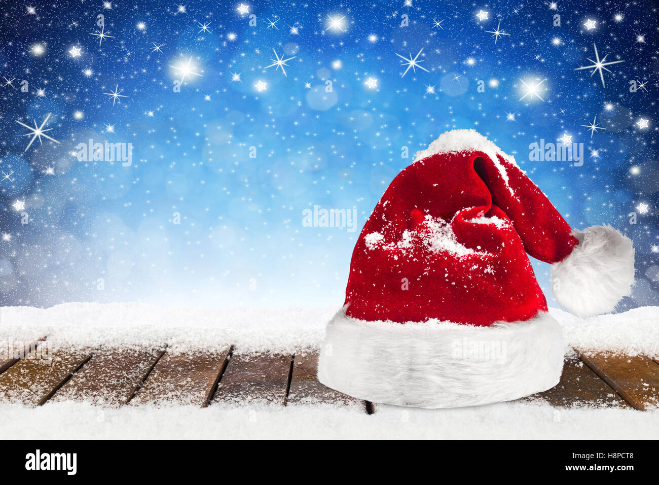 86b70bc55009e christmas xmas background with santa claus hat cap on wooden snowy planks  in front of blue night sky stars and snowflakes