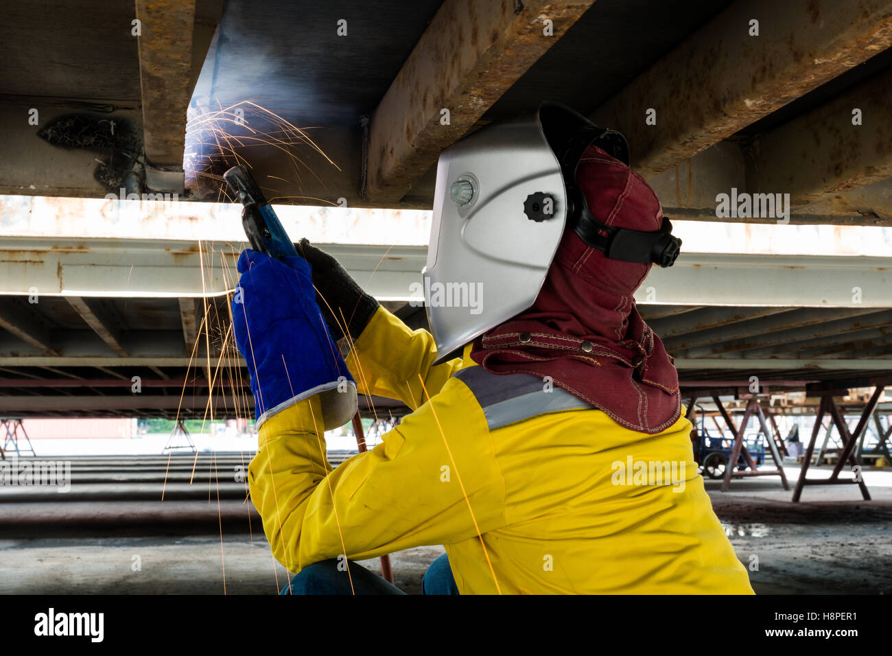 Industry worker with welding steel to repair container structures manufacture workshop in industry factory. - Stock Image