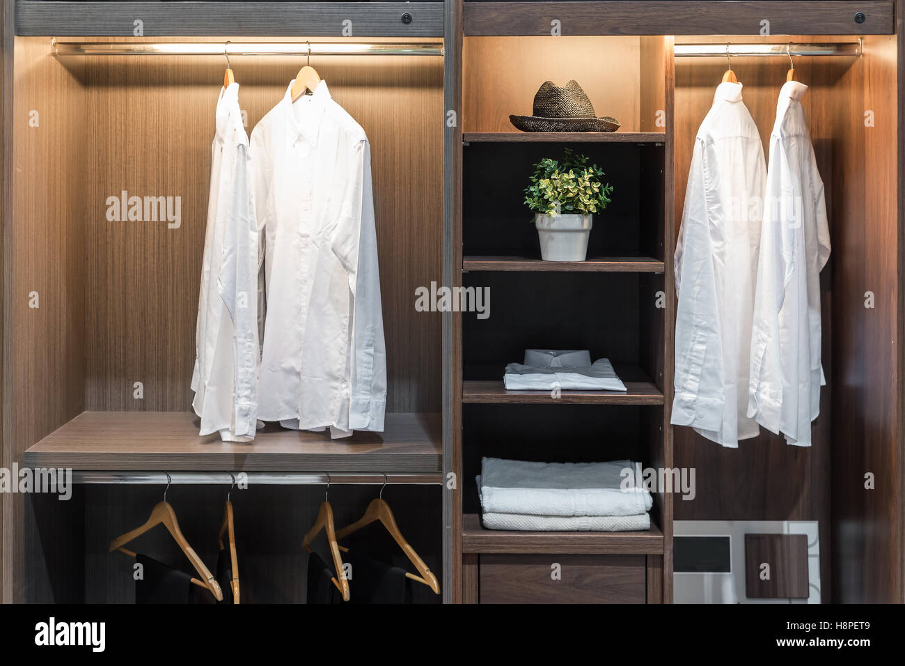 Modern interior wardrobe with shirt, pants, hat and towel in shelf. - Stock Image