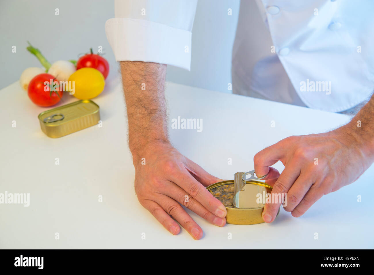 Chef opening a can. - Stock Image