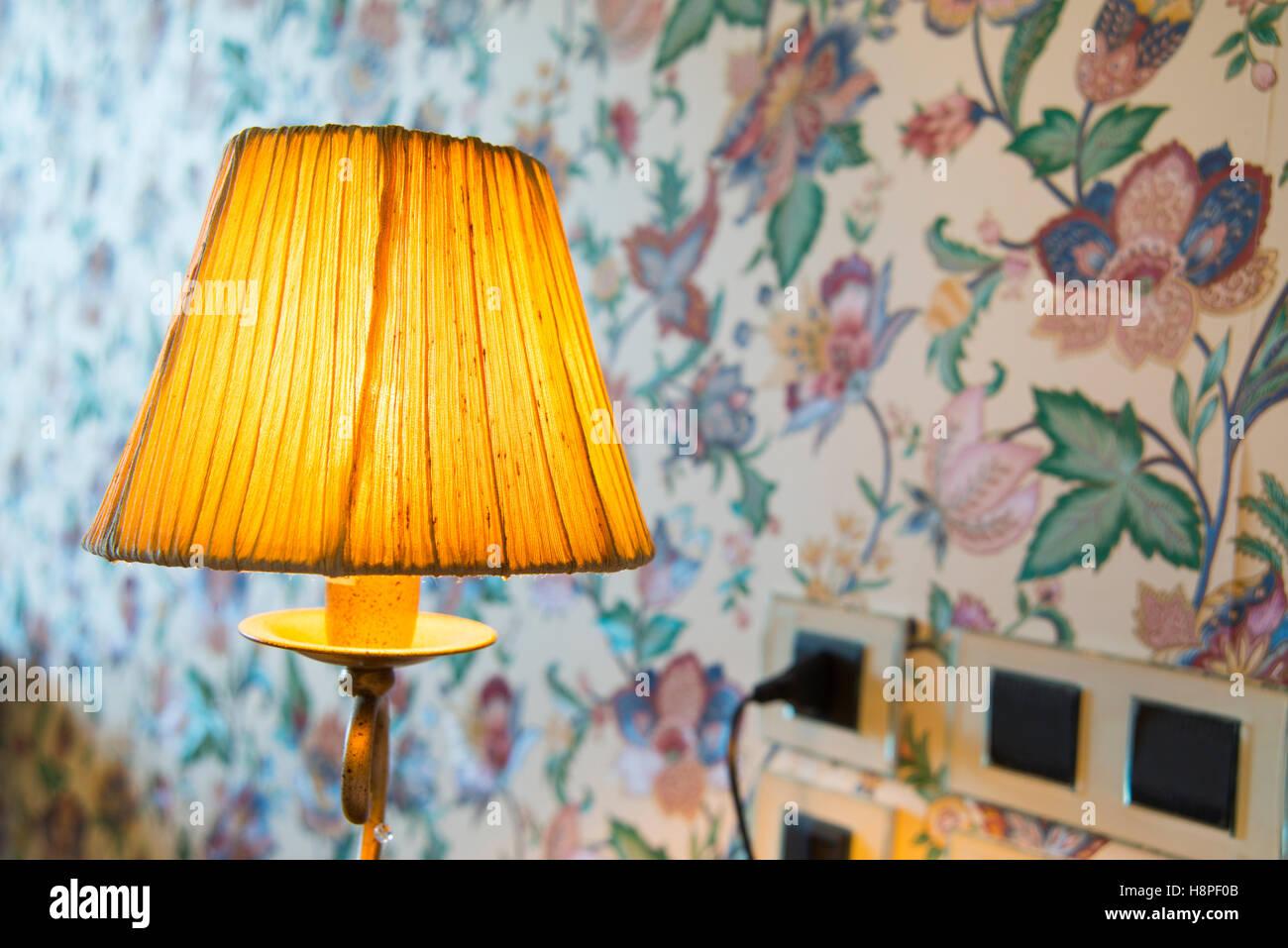 Lit bedside lamp. - Stock Image
