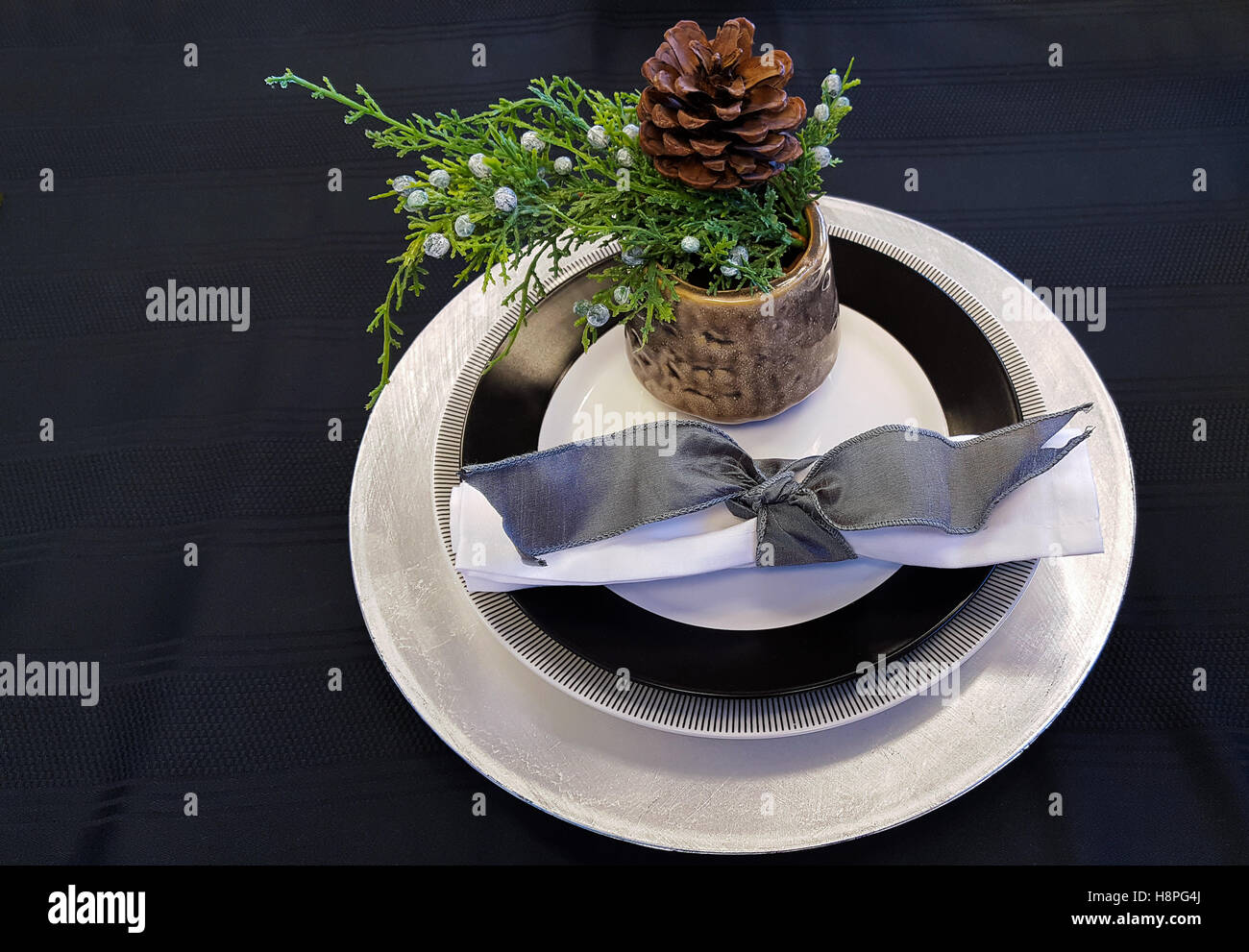 Evergreen In Cup With Christmas Plate Setting On Black Tablecloth Stock Photo Alamy