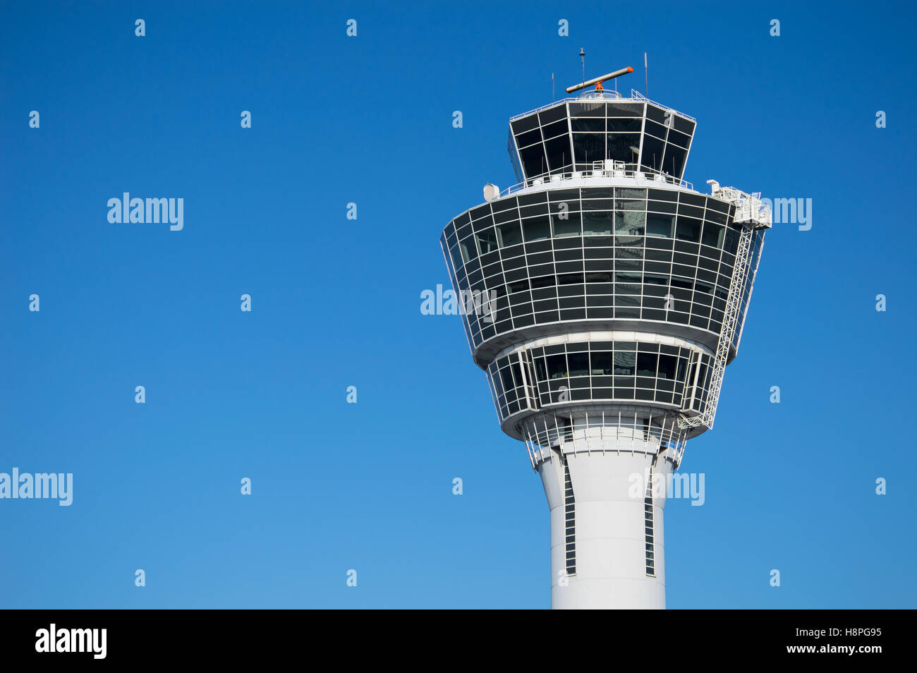 Modern air traffic control tower in international passenger airport over clear blue sky - Stock Image