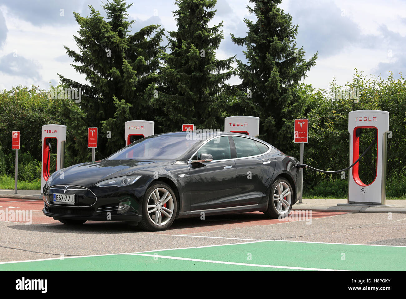 PAIMIO, FINLAND - JULY 17, 2016: Black Tesla Model S Electric car charging at Tesla Supercharger station in Paimio, Stock Photo