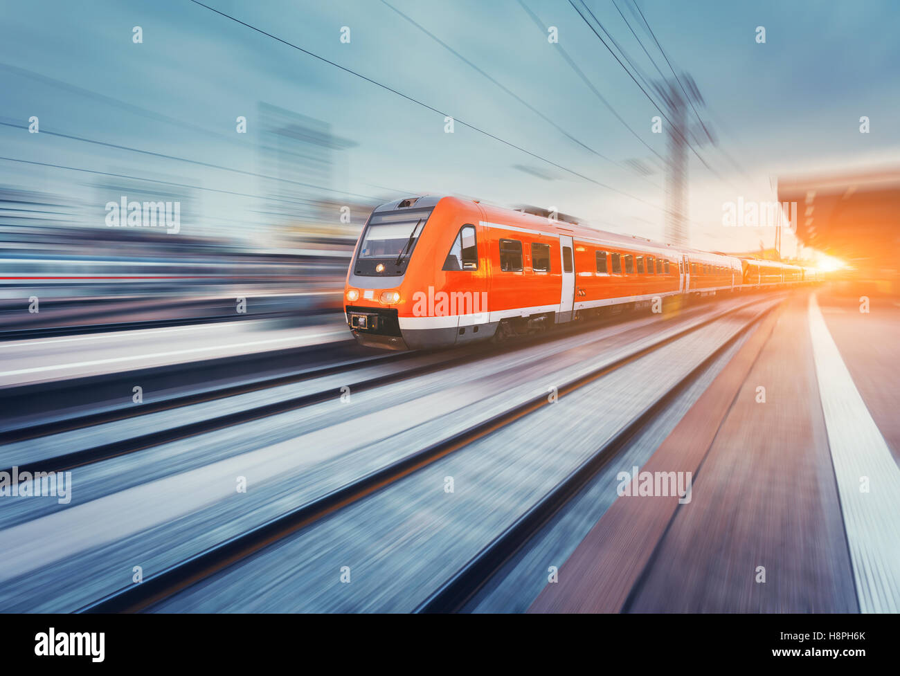 Modern high speed red passenger commuter train in motion at the railway platform at sunset. Railway station. Railroad - Stock Image