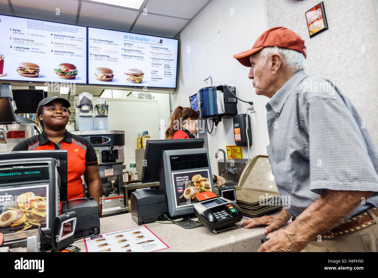 Vero Beach Florida McDonald's restaurant fast food interior counter cashier Black teen girl employee senior man Stock Photo
