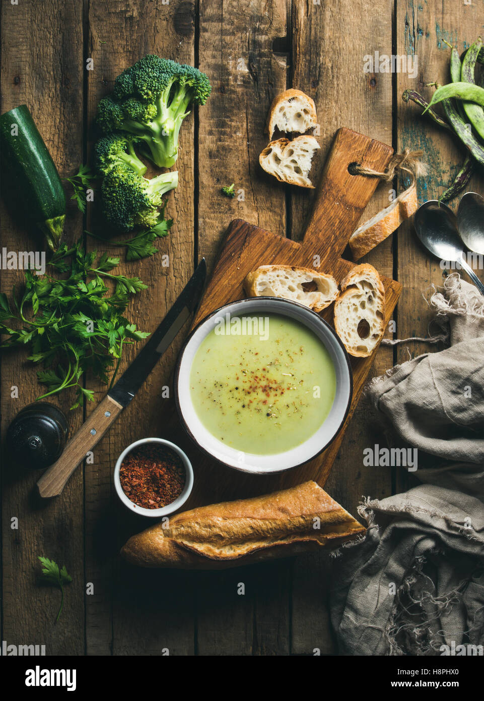 Homemade pea, broccoli, zucchini cream soup with fresh baguette - Stock Image