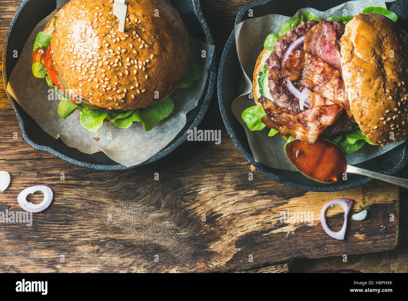 Homemade beef burgers with crispy bacon and vegetables in pans - Stock Image