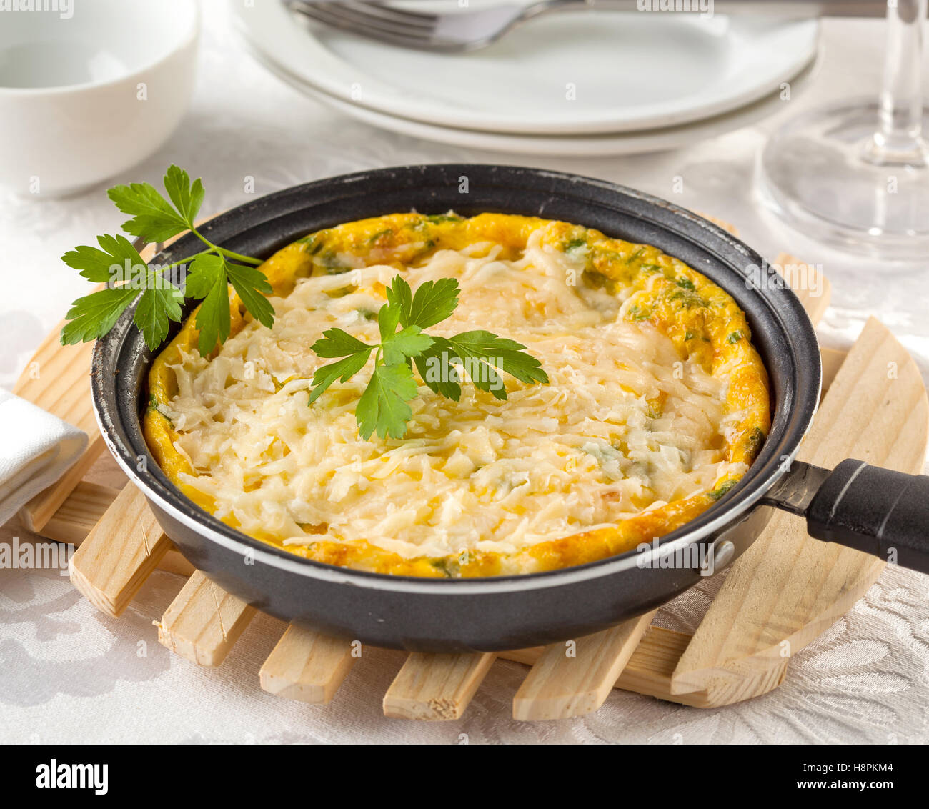 Italian frittata with ricotta, cheddar, gruyere and parmesan cheese in a frying pan on a table. - Stock Image