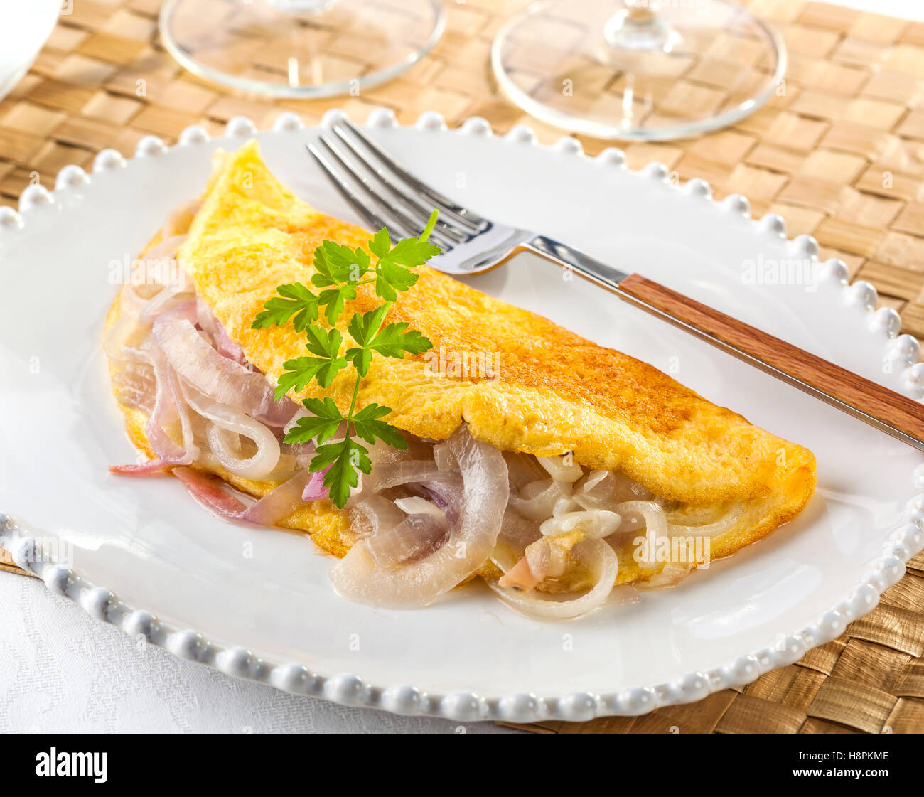Delicious egg omelet filled with fried onions on a plate. Breakfast or brunch. - Stock Image