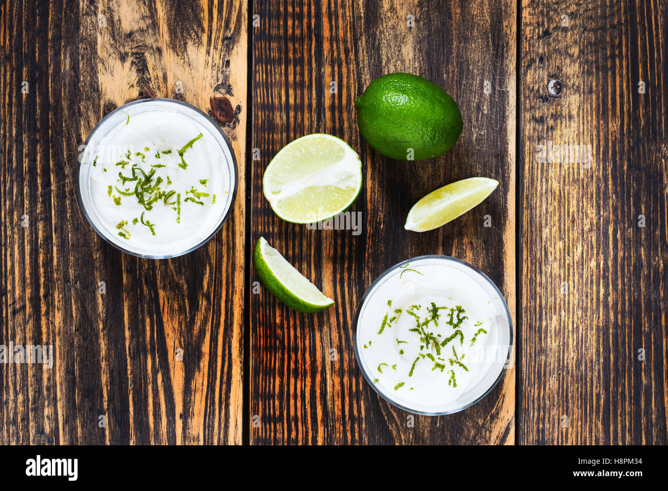 Raw  lime cheesecake in a glass on wooden table viewed from above. Rustic background with free text space - Stock Image