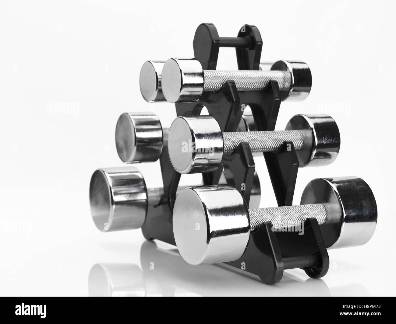 Rack with a set of shiny chrome dumbbells - Stock Image