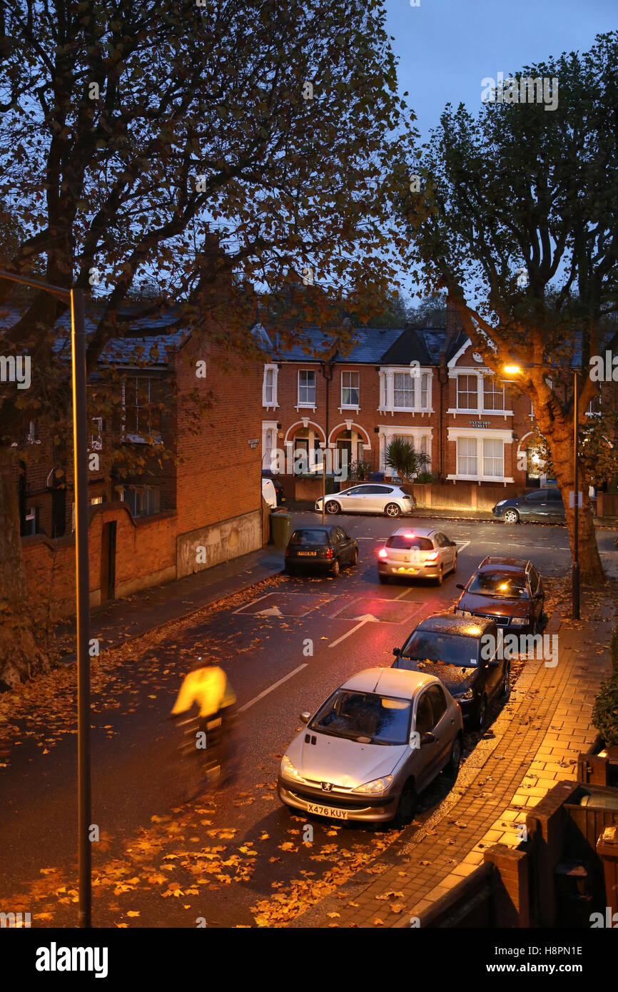 Autumn leaves cover the pavements and streets in a typical South London street after dark on a wet night. A cyclist - Stock Image