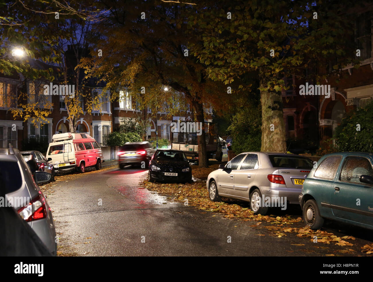 Autumn leaves cover the pavements and streets in a typical South London street after dark on a wet night - Stock Image