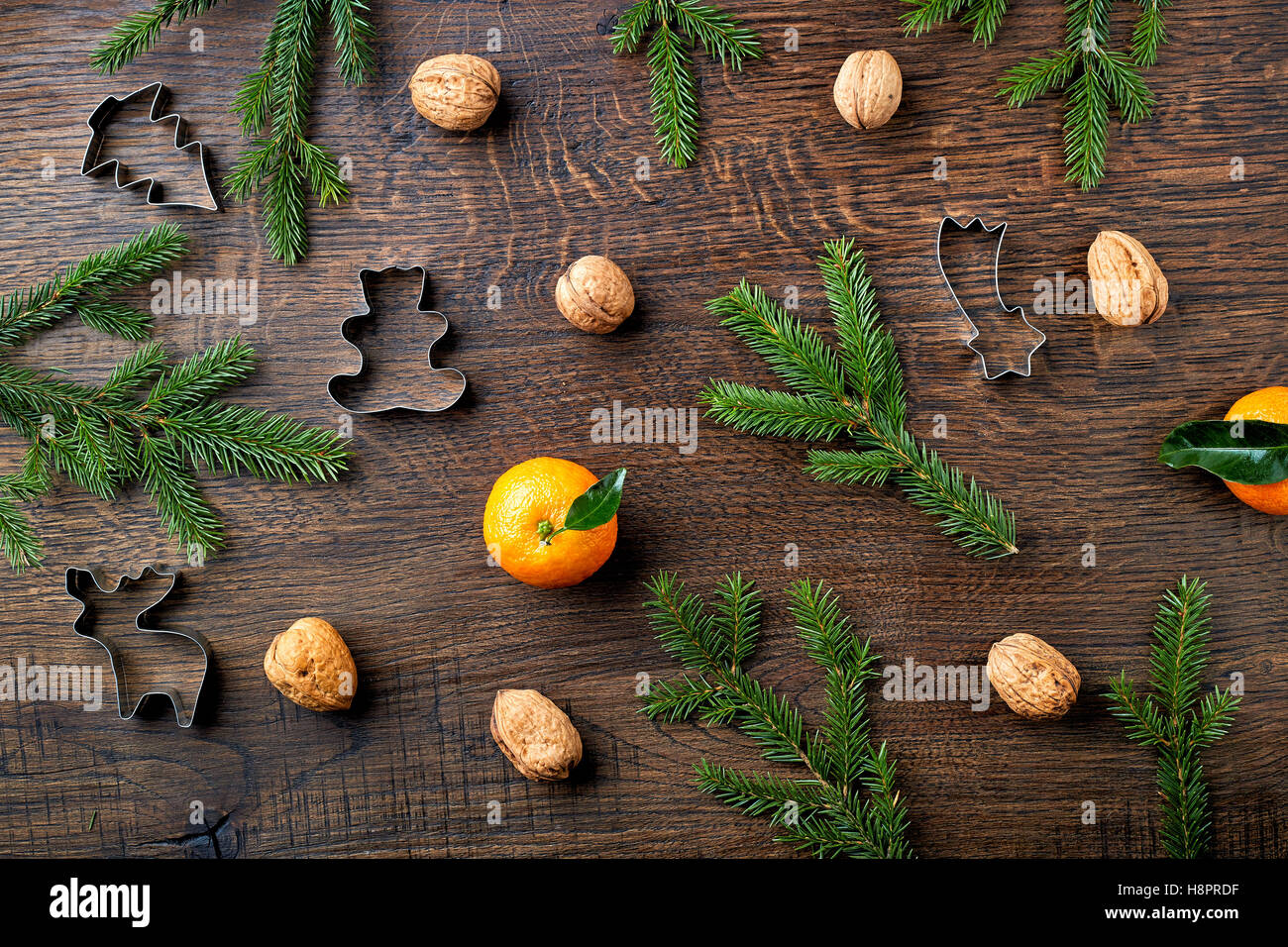 Christmas background with spruce branches, oranges, walnuts and cookie cutters - Stock Image