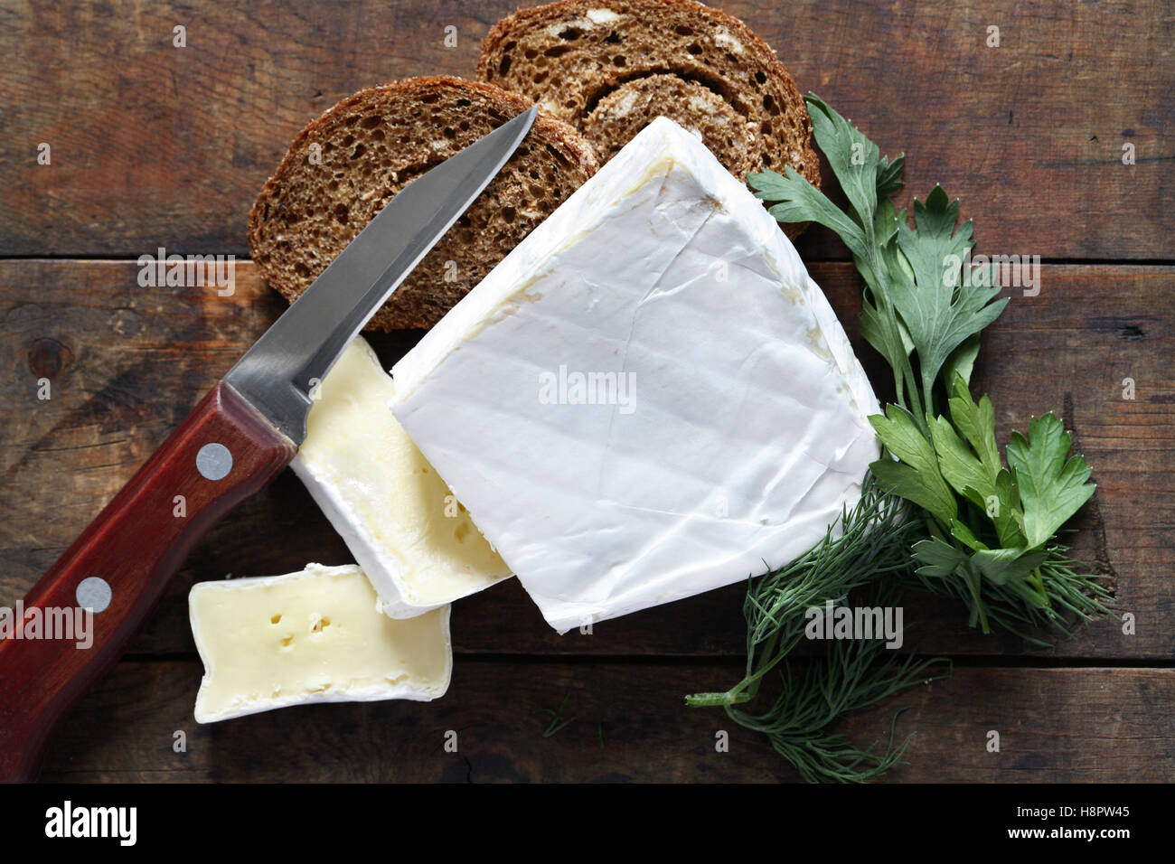 Piece of french brie cheese near knife and bread on old wooden background - Stock Image