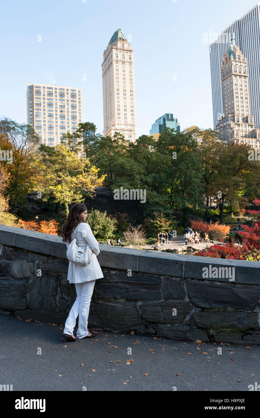 Single Caucasian female dressed in a white outfit admiring the New York City skyline from a bridge in Central Park. - Stock Image