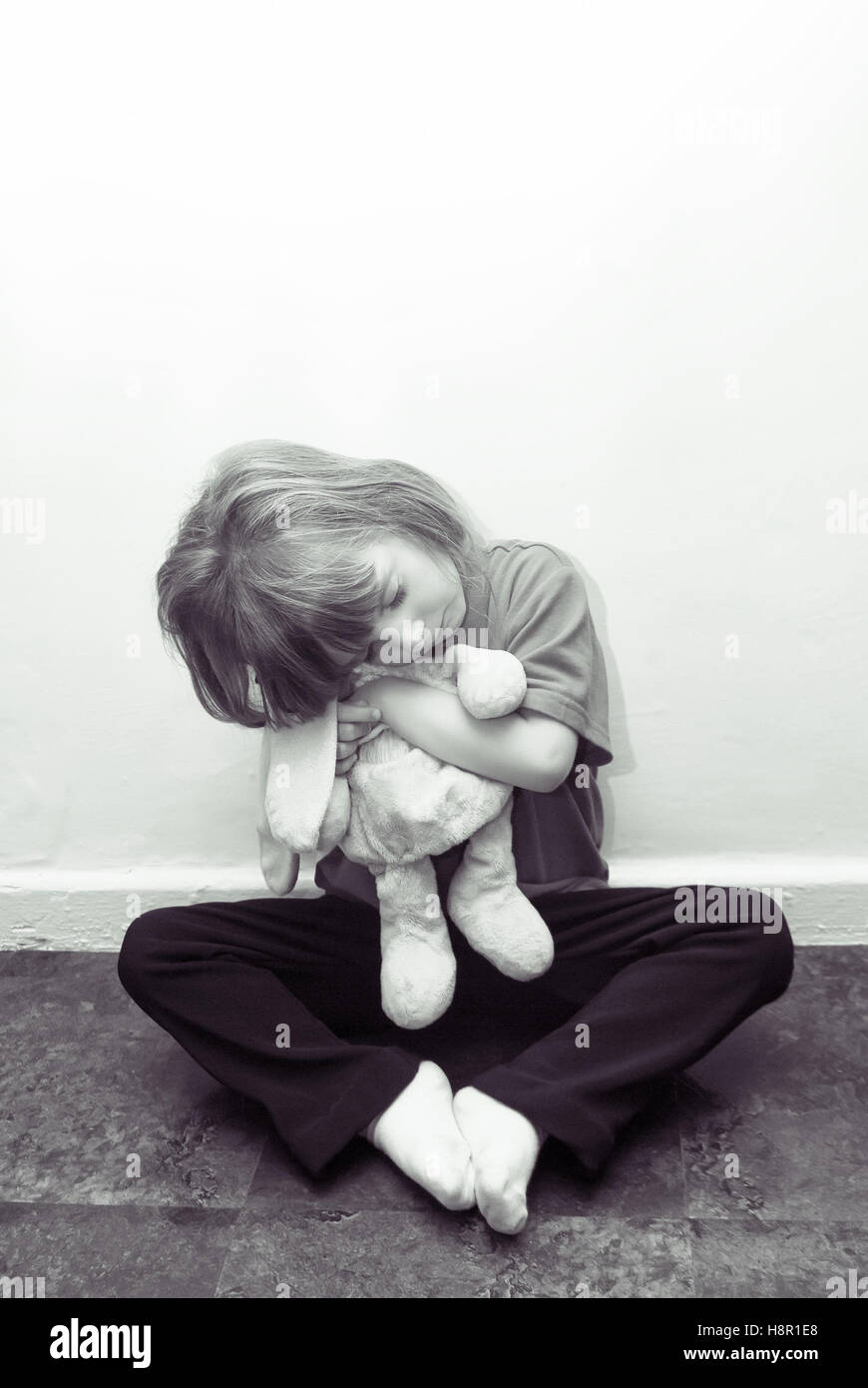 A conceptual image of a very upset little girl, sitting on the floor cuddling a soft toy. - Stock Image