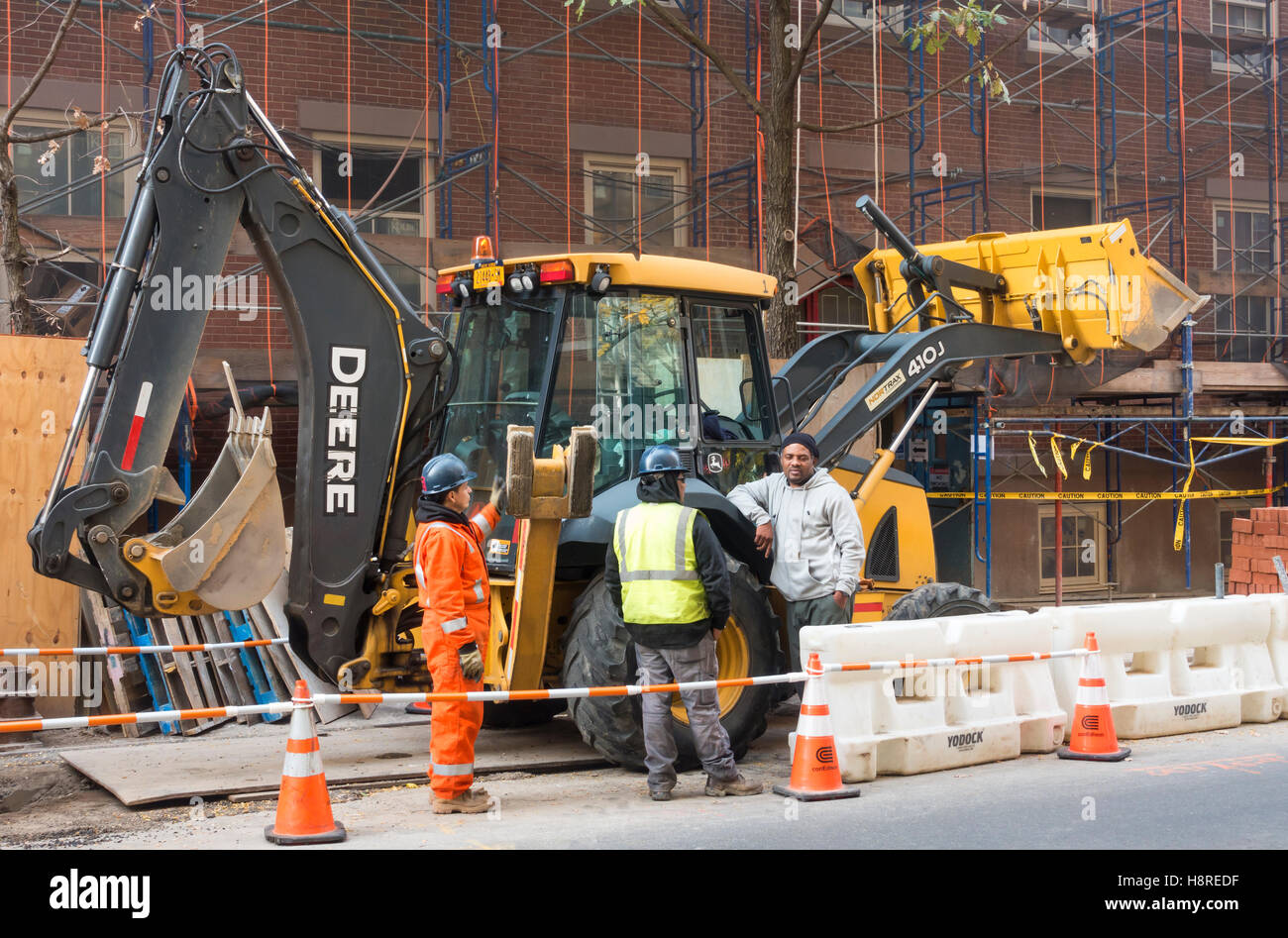 John Deere 410J with construction workers on a work site in New York City - Stock Image