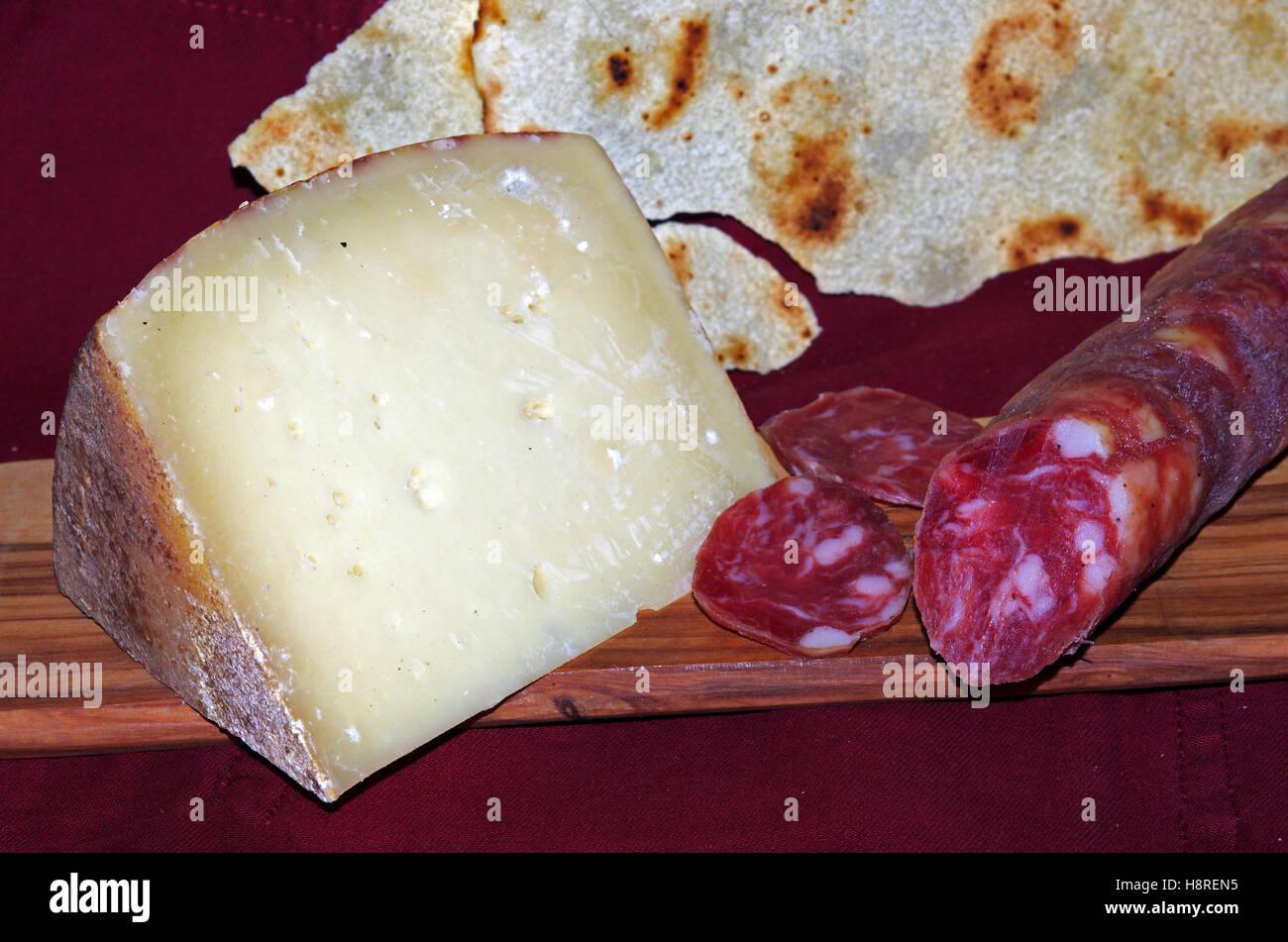 Sardinian typical products: pecorino chese, pork-sausage and pane carasau - Stock Image