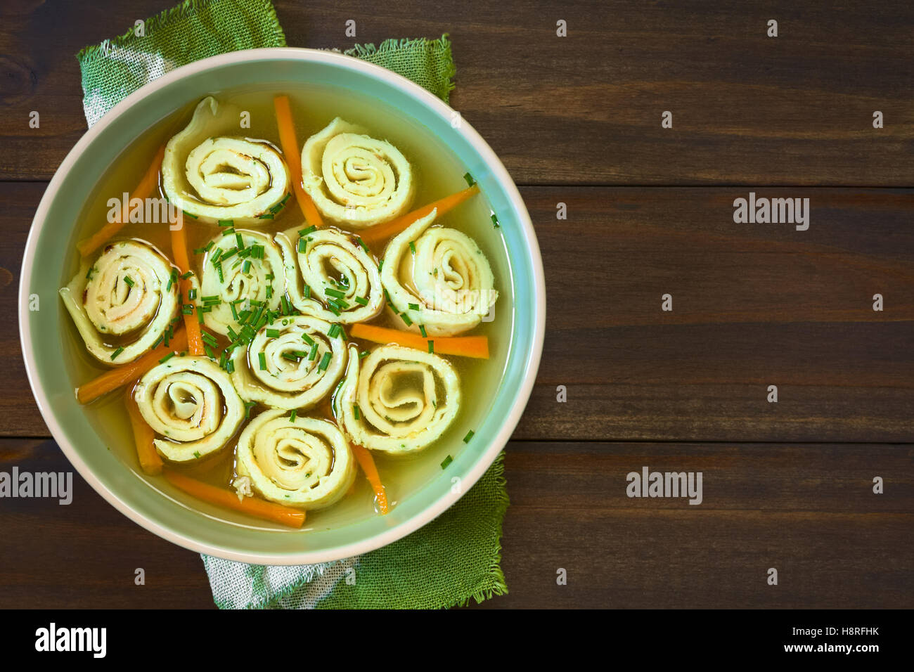 Traditional German Flaedlesuppe and Austrian Frittatensuppe consomme with rolls or stripes of pancake or crepe with - Stock Image