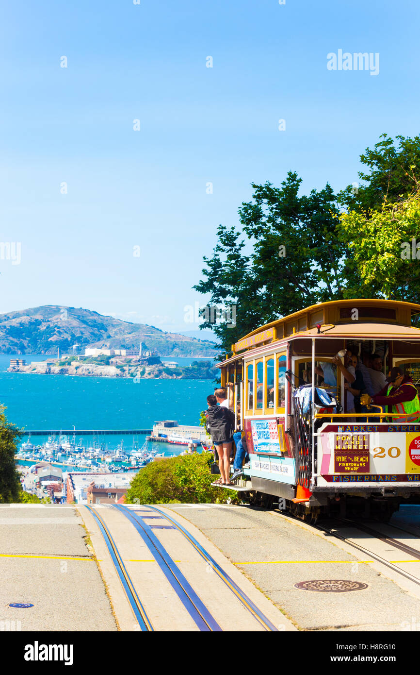 An iconic cable car full of passengers at the crest of Hyde Street going over the edge toward the view of Alcatraz - Stock Image