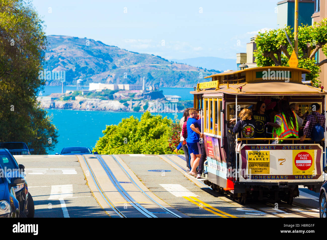 Telephoto compressed view of Alcatraz Island and cable car full of tourist passengers at crest of Hyde Street on - Stock Image