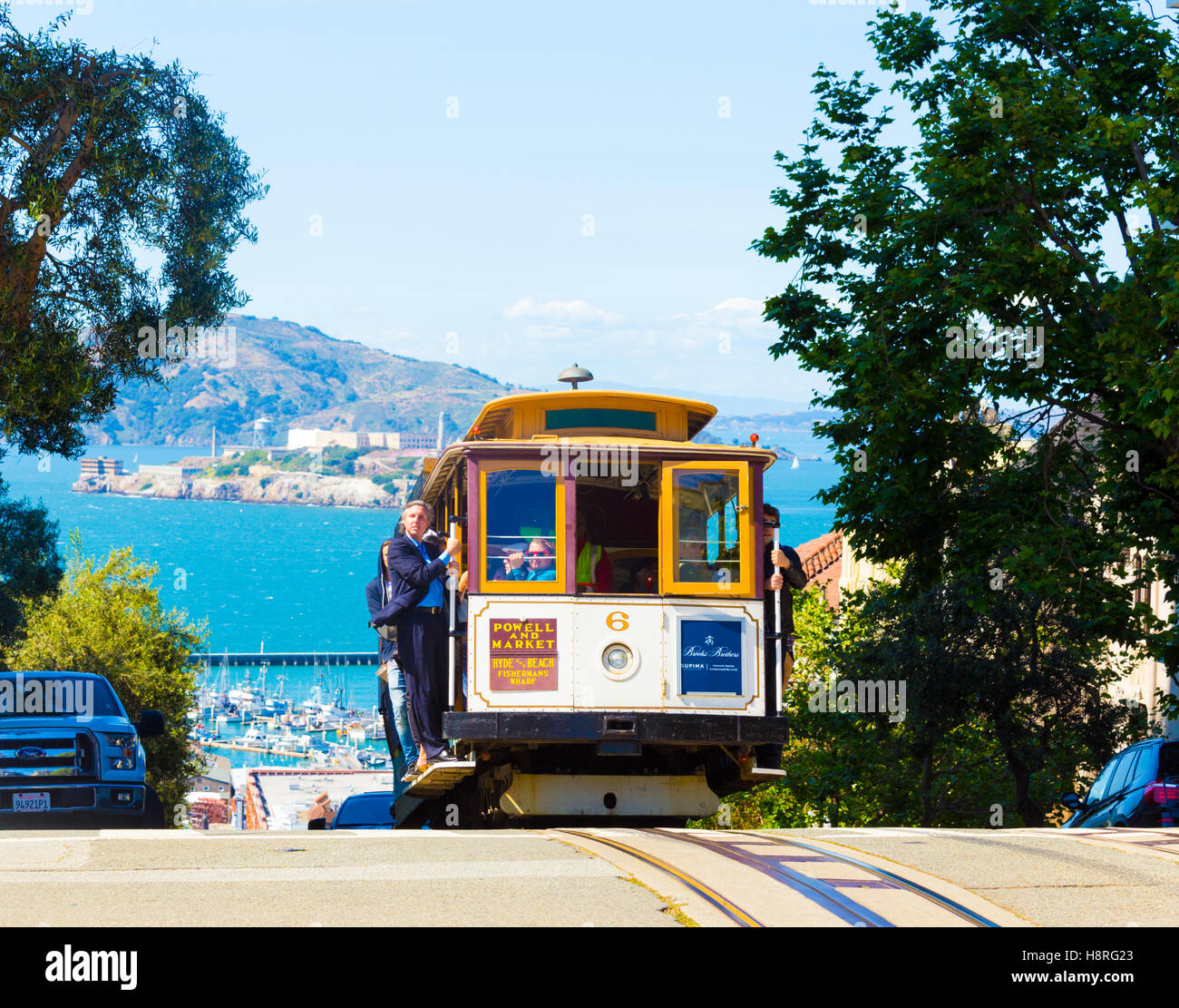 Approaching cable car climbing over crest of hill with Alcatraz Island in background - Stock Image