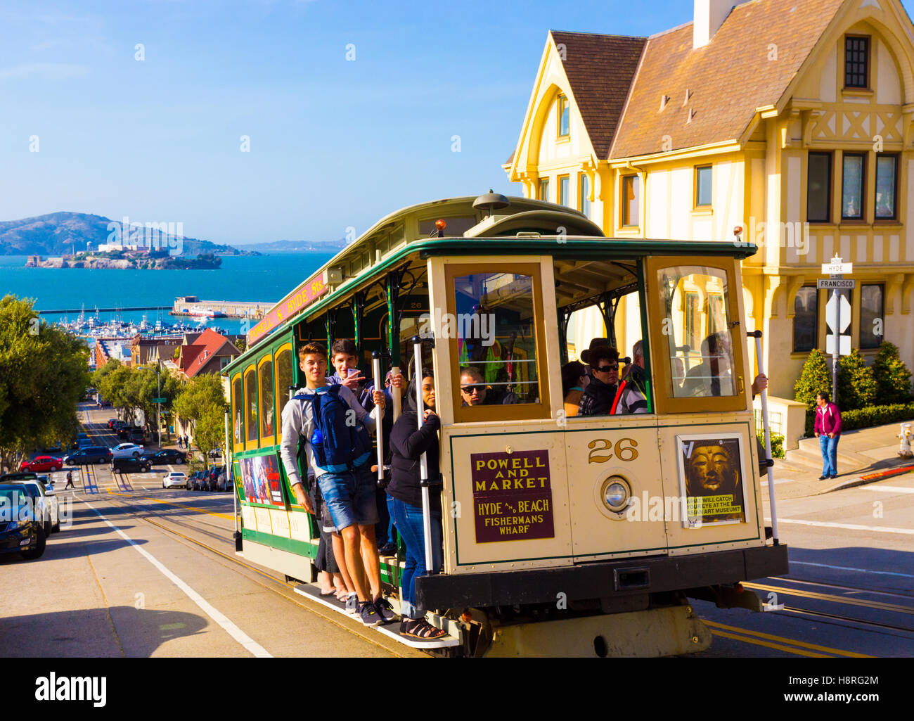 Closeup of approaching Hyde Street cable car full of people standing on outside platform enjoying steep hill ride - Stock Image
