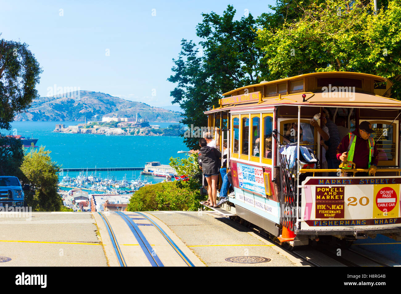 A cable car full of tourists at the peak of Hyde Street going over the edge toward the view of Alcatraz Island in - Stock Image